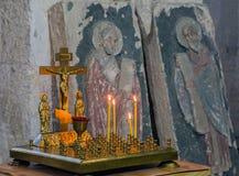 Helgdagsafton med stearinljus och ett kors i kyrkan Royaltyfria Bilder