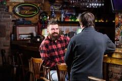 Helgfritid fredag avkoppling i bar Vänner som kopplar av i bar Vänlig konversation med främlingen Brutal Hipster arkivbild