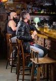 Helglivsstil Sitter den skäggiga mannen för grabben på stångräknaren i bar Stort ställe för bar som äter middag drinken och som h royaltyfri foto
