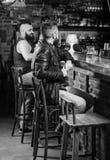 Helglivsstil Sitter den skäggiga mannen för grabben på stångräknaren i bar Stort ställe för bar som äter middag drinken och som h royaltyfria foton