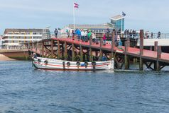 Ferry with passengers leaving harbor Helgoland to nearby island Dune. Stock Photography