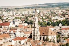Helgon Michael Catholic Gothic Church i den Unirii fyrkanten och gammal historisk medeltida mitt av Cluj-Napoca Arkivfoto