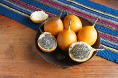 Helhet och halv passionfrukt med frö i en bunke Royaltyfria Bilder