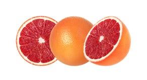Helhet och halva rosa grapefrukter som isoleras på vit bakgrund arkivbilder