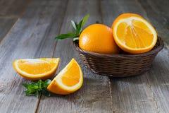Helhet och klippta apelsiner med mintkaramellsidor Royaltyfri Fotografi