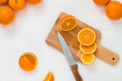 Helhet och klippta apelsiner, skivor av apelsinen på träbräde på den vita torkduken Royaltyfria Bilder