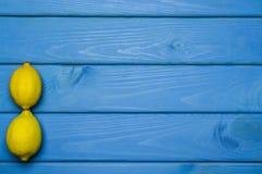 Helhet och klippta citroner i beställning på blå träyttersida Fotografering för Bildbyråer