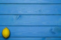 Helhet och klippta citroner i beställning på blå träyttersida Royaltyfri Foto