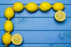 Helhet och klippta citroner i beställning på blå träyttersida Royaltyfri Bild