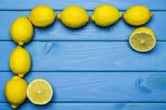Helhet och klippta citroner i beställning på blå träyttersida Royaltyfri Fotografi