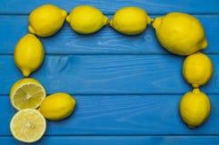 Helhet och klippta citroner på blå träyttersida Fotografering för Bildbyråer