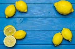 Helhet och klippta citroner på blå träyttersida Royaltyfri Foto