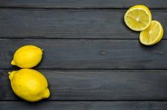 Helhet och klippta citroner på grå träyttersida Royaltyfri Bild
