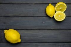Helhet och klippta citroner på grå träyttersida Royaltyfria Bilder
