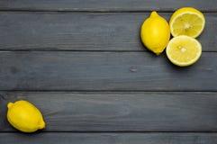 Helhet och klippta citroner på grå träyttersida Arkivfoton