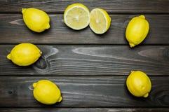 Helhet och klippta citroner på grå träyttersida Arkivfoto