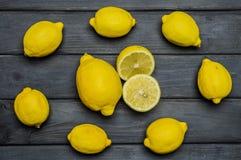 Helhet och klippta citroner på grå träyttersida som är ordnad i cirkel Royaltyfri Bild