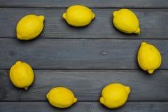 Helhet och klippta citroner på grå träyttersida som är ordnad i cirkel Arkivbild