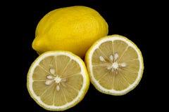 Helhet och klippta citroner på svart bakgrund Arkivbild