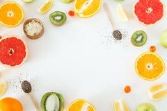 Helheten och halva citrusfrukter och äpplen ligger på en vit bakgrund Royaltyfri Foto