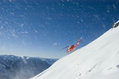 Heli-skiing in BC. A helicopter flies from atop the Cariboo Mountains stock photography