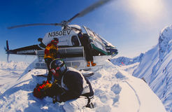 Heli-skiing in the Chugach Mountains of Alaska. VALDEZ, ALASKA - APRIL 22: Snowboarder Esben Pedersen being dropped of by helicopter onf an isolated peak in the royalty free stock photography