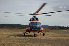 Helicóptero alaranjado no aeródromo Foto de Stock