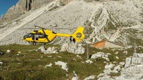 Helicóptero amarelo usado para operações de salvamento, na terra nas dolomites, Itália Salvamento por helicóptero Fotografia de Stock Royalty Free