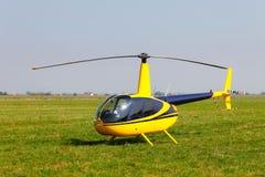 Helicóptero amarillo en campo Fotografía de archivo