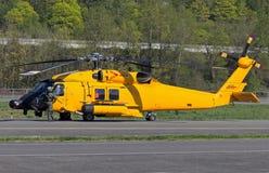Helicóptero amarillo que se sienta en la pista de despeque con el equipo Imagen de archivo