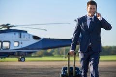 Helicóptero de Walking Away From del hombre de negocios mientras que habla en Mobil Imágenes de archivo libres de regalías