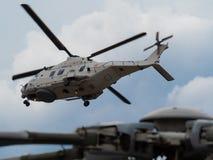 Helicóptero del rescate NH90 de la marina de guerra belga en el fondo, con un cierre para arriba del rotor de un helicóptero colo imagenes de archivo