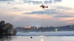 Helicóptero do ministério das situações de emergência O helicóptero recolhe a água no rio para extinguir um fogo E video estoque