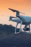 Helicóptero do quadrilátero do zangão com a câmara digital no por do sol pronto para voar para Imagem de Stock Royalty Free