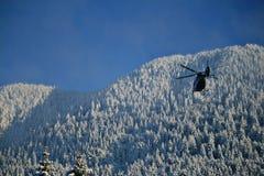 Helicóptero en la acción en un día de invierno soleado trabajo para rescatar a gente el días de fiesta de la Navidad foto de archivo