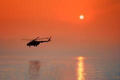 Helicóptero en la puesta del sol Fotos de archivo