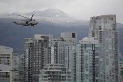 Helicóptero militar sobre horizonte de la ciudad Fotos de archivo
