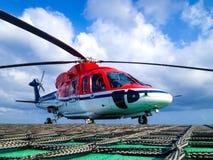 Helicóptero no helideck a pouca distância do mar Fotos de Stock Royalty Free