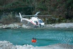 Helicóptero que recoge el agua en un cubo Fotos de archivo libres de regalías
