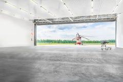 Helicóptero que se coloca delante del hangar Imagenes de archivo