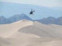 Helicóptero que vuela sobre las dunas de arena de las dunas de Dumnot Imagen de archivo libre de regalías