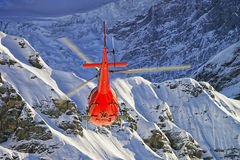 Helicóptero rojo en las montañas suizas cerca de la montaña de Jungfrau Fotografía de archivo libre de regalías