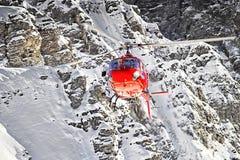 Helicóptero rojo en las montañas suizas cerca de la montaña de Jungfrau Foto de archivo