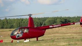 Helicóptero rojo que saca de un campo metrajes