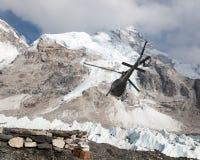 Helicopper dans le camp de base et le bâti Nuptse du mont Everest Photographie stock