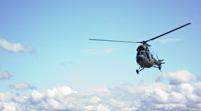 Helicopter. Green helicopter on a blue sky with clouds Stock Image