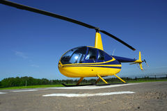 Helicopter. Yellow - Blue helicopter standing in the airport Stock Images