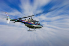 Helicopter. With a strong zoom against a blue and cloudy sky Stock Photo
