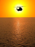 Helicopter. A helicopter flying in sunsetting sky over sea Stock Images