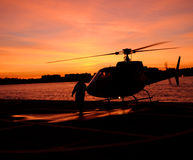 Helicopter. Scenic view of helicopter and person silhouetted by side of ocean, sunset scene Stock Photo